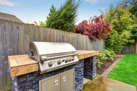 areas: Close-up Of Barbecue gas Appliance in the backyard garden. House exterior.