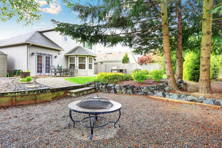 fire pit: Large backyard with beautiful landscape and fire pit. House exterior.