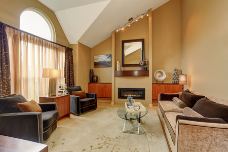 furnished: Beautiful brown and beige living room with vaulted ceiling. Furnished with nice sofa, glass coffee table, cabinets and fireplace