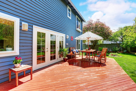 house siding: Wooden walkout deck in the backyard garden of blue siding house. Furnished with patio table set with umbrella