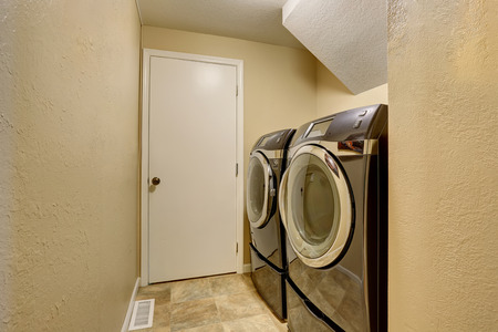 black appliances: Small beige laundry room with black modern appliances and tile floor