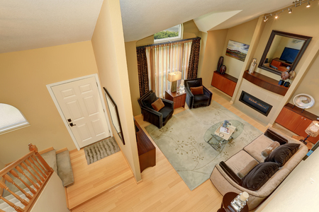 upstairs: Panoramic view of elegant living room and entryway from upstairs. High vaulted ceiling and light tones hardwood floor
