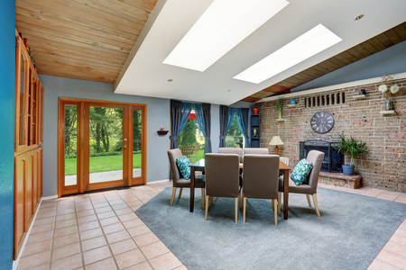 stone fireplace: Light spacious dining room with stone tile wall and built-in fireplace, skylight, tile flooring and view of back yard.