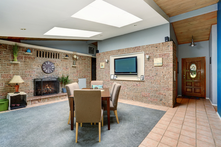 stone fireplace: Light spacious dining room with stone tile wall and built-in fireplace, skylight, tile flooring and view of entrance door Stock Photo