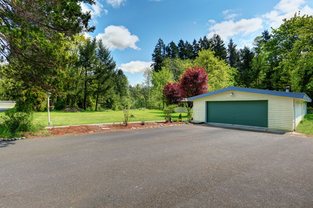 Wide asphalt driveway with green door garage and beautiful landscape