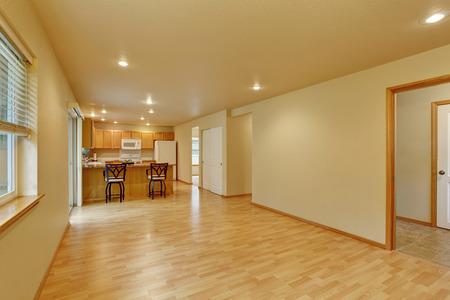 hardwood floor: Spacious empty room with hardwood floor connected to kitchen Stock Photo