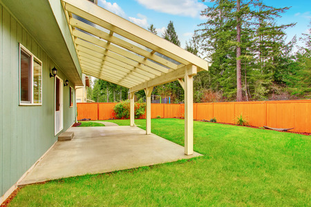 fenced: Covered backyard patio with concrete floor. Fenced brown backyard and well kept green lawn around