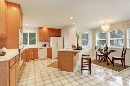 shiny floor: Kitchen room interior with brown cabinets, tile floor, island and dining area