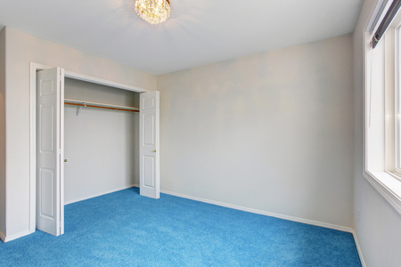 blue carpet: Empty luxury room interior with blue carpet floor and beautiful chandelier. White opened doors of built-in closet Stock Photo
