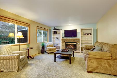 Light beige living room with sofa, armchair and cozy fireplace 版權商用圖片 - 60403421