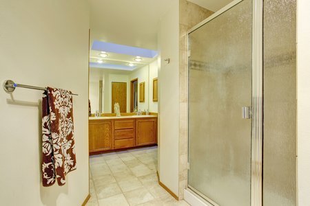 bathroom tile: Nice master bathroom with brown cabinets and tile floor. Stock Photo