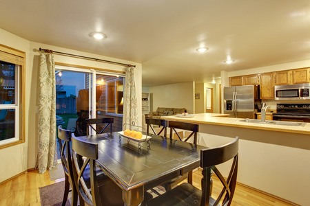 Dining room area connected to kitchen with black table set Stock Photo