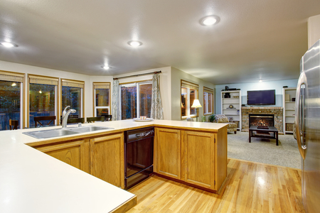 Open floor plan kitchen interior with brown cabinets and hardwood floor. Also connected to living room with fireplace
