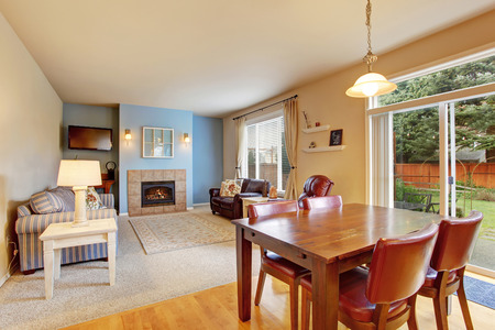 Cozy living room with carpet floor and fireplace. Also dining area