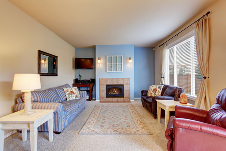 family rooms: Cozy living room with carpet floor, fireplace and rug. Blue painted wall Stock Photo