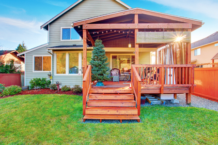 Back yard house exterior with wooden walkout deck and porch