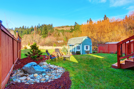 desing: Fenced back yard with nice landscaping desing and blue barn shed. patio area