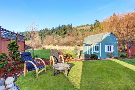fenced: Fenced back yard with nice landscaping desing and blue barn shed. patio area