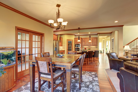 Open floor plan dining area connected to kitchen and living room. Wooden table set and nice rug Stock Photo