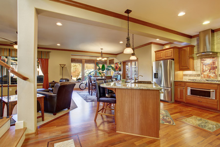 open floor plan: Open floor plan interior with living room, kitchen and dining area. Hardwood floor and leather armchairs