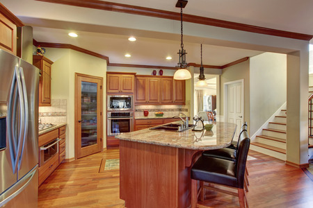 kitchen counter top: Kitchen interior with island. Wooden cabinets with granite counter top and hardwood floor Stock Photo