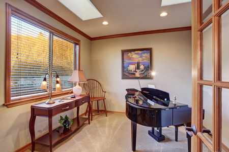 country house style: Piano room with antique furniture and carpet floor. Old black shiny piano