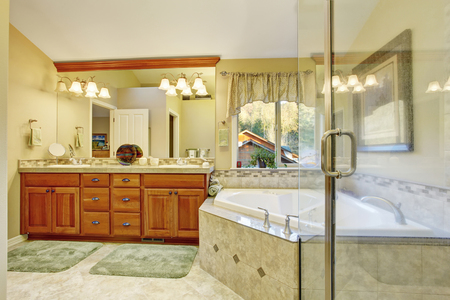 brown granite: Luxury bathroom interior with tile floor. Bath tub with brown granite tile trim and vanity cabinet with large mirror.