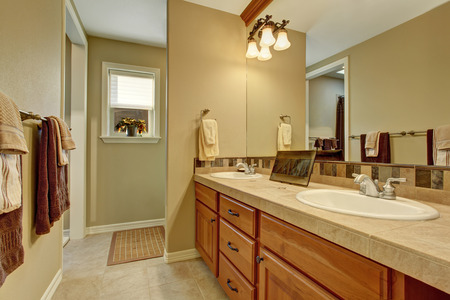 bathroom tile: Bathroom interior with wooden cabinets, tile floor and big mirror Stock Photo