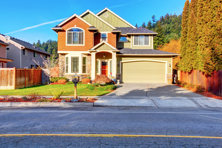 appeals: Classic house with garage, driveway, and grassy front yard. Curb appeal Stock Photo