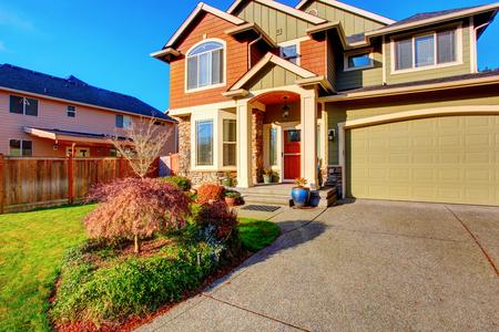 portada: Casa clásica con garaje, camino de entrada, y el patio frontal de hierba. Atractivo exterior Foto de archivo