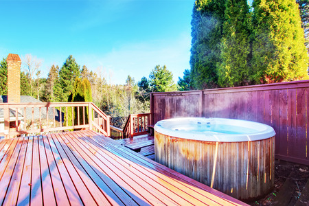 Fenced backyard area with hot tub and wooden walkout deck