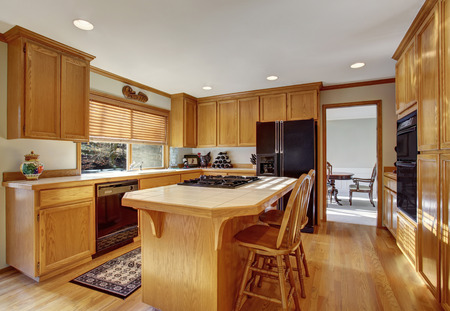 cabinets: Kitchen room interior with wooden cabinets, light tone hardwood floor and island