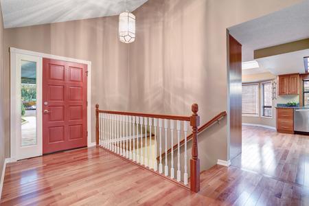 puerta de entrada simple, con piso de madera y escalera. Puerta de entrada roja
