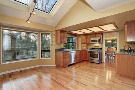 kitchen cabinets: Kitchen with nice counters, stained cabinets and hardwood floor Stock Photo