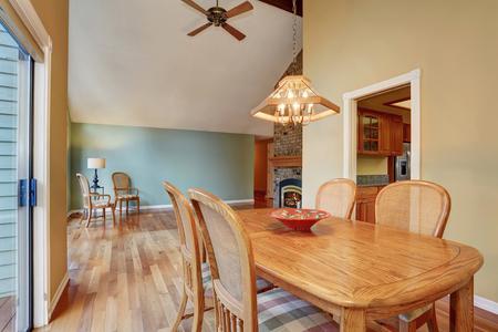 comedor con juego de mesa, piso de madera. Conectado a la zona de descanso con chimenea y cocina aslo