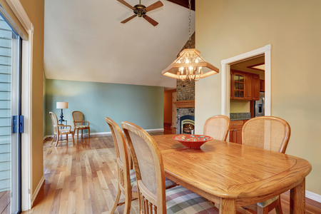 areas: Dining area with table set, hardwood floor. Connected to rest area with fireplace and aslo kitchen