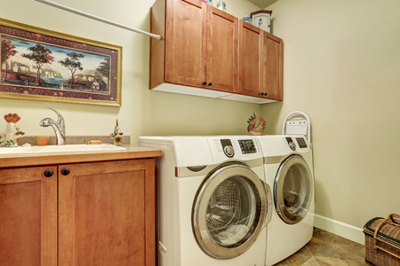 laundry room: Laundry room with modern appliances, brown vanity cabinet with drawers.