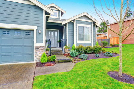 curb appeal: Curb appeal. House exterior with blue trim, garage and driveway