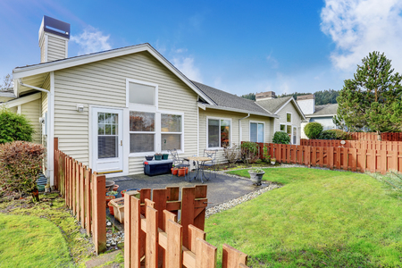 yard: Back yard concrete patio area. Wooden fence and well kept lawn around Stock Photo