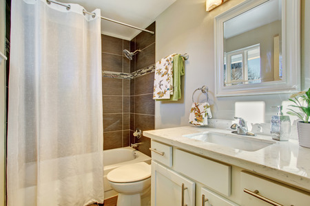 bathroom tile: Bathroom interior with white cabinets, tile floor and bath tub Stock Photo