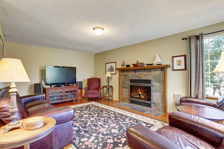 floor rug: Living room interior with fireplace, hardwood floor, rug and leather sofa
