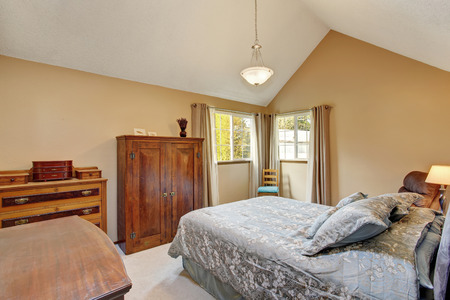 sharpen: Bedroom interior with old sharpen furniture, carpet floor and beige walls