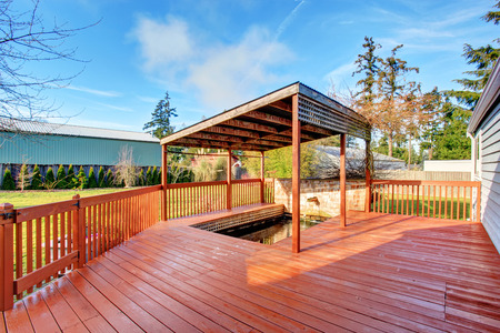 Large back yard with grass, covered wooden deck and grass. Stock Photo