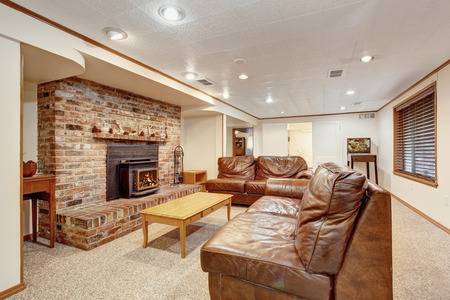 Cozy living room with leather sofa, carpet floor and fireplace