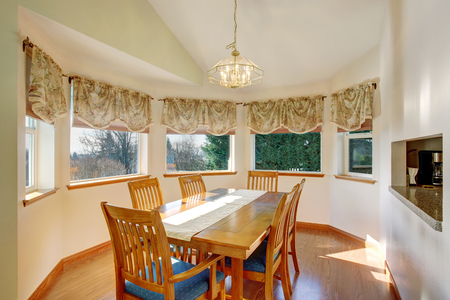Dining room interior with wooden table set, hardwood floor and windows around