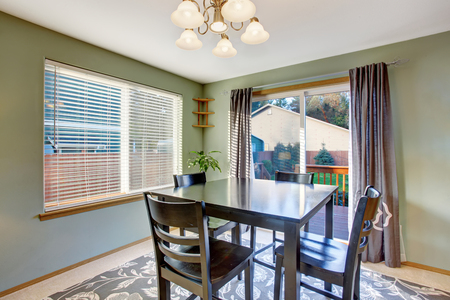 designer chair: Dining area in green tones with black table set and carpet floor