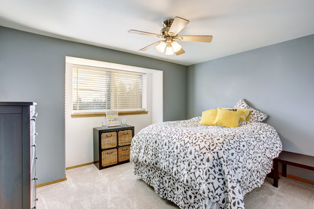 yellow walls: Bedroom interior with walls in blue tones and carpet floor. Also big bed with yellow pillows