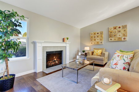 fireplace living room: Cozy living room with hardwood floor, fireplace and beige sofa Stock Photo