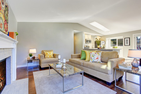 Cozy living room with hardwood floor, fireplace and beige sofa. Open plan living room connected to kitchen