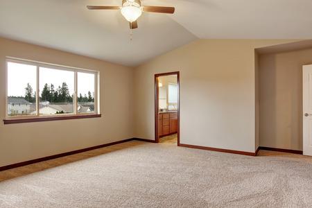 remodeled: Empty room interior with carpet floor, opened door and beige walls